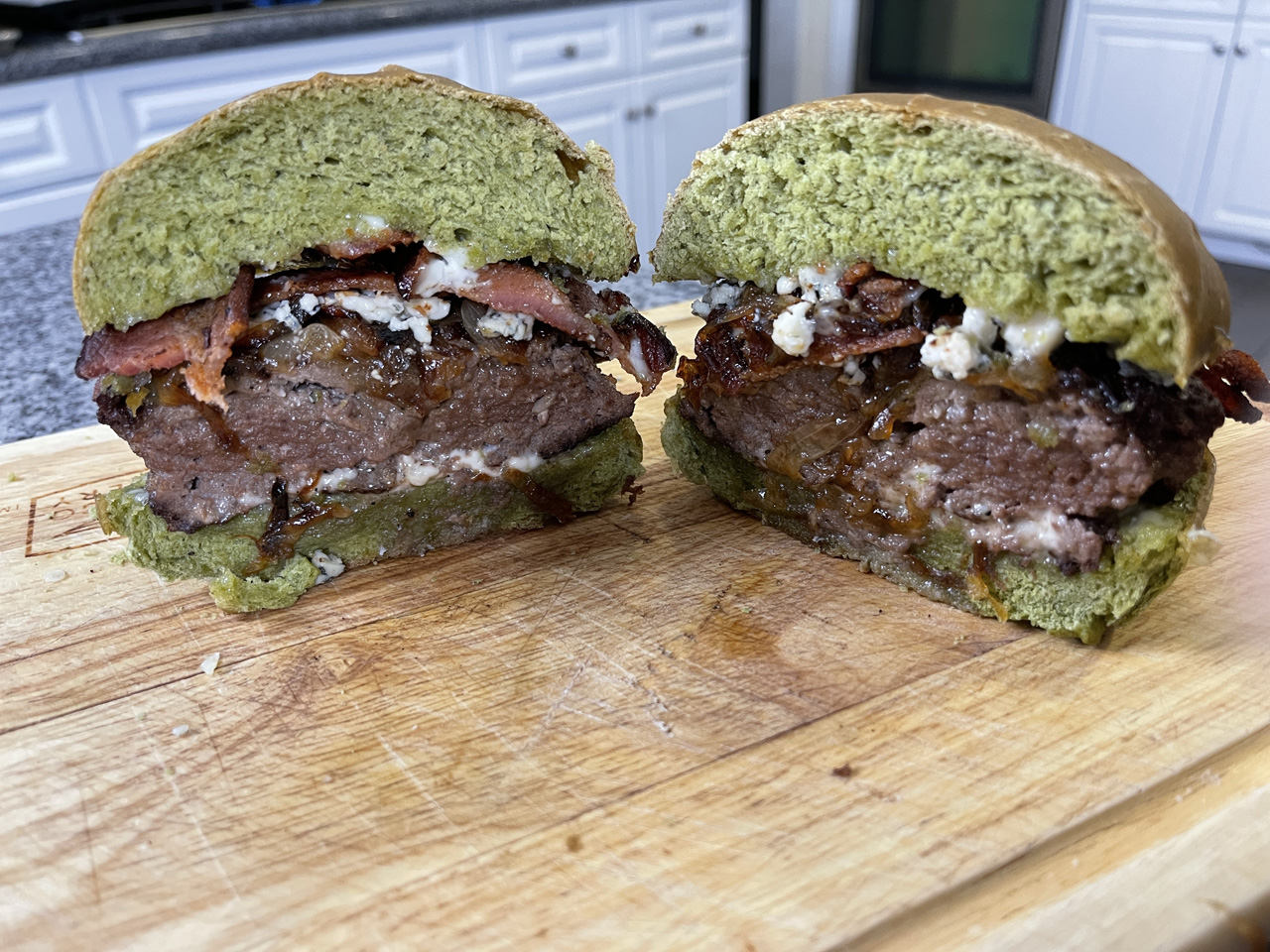 Photo of Completed Spinach Bun and Burger cut in half with Crisp Bacon, Carmelized Onions, and Blue Cheese