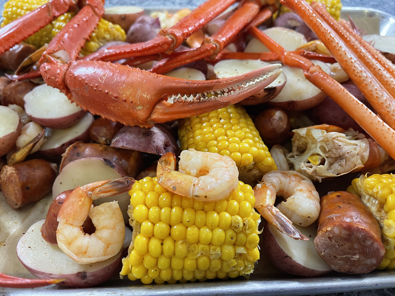 Close-Up Photo of the Crab Legs and Claw, Shrimp, Potatoes, and Corn