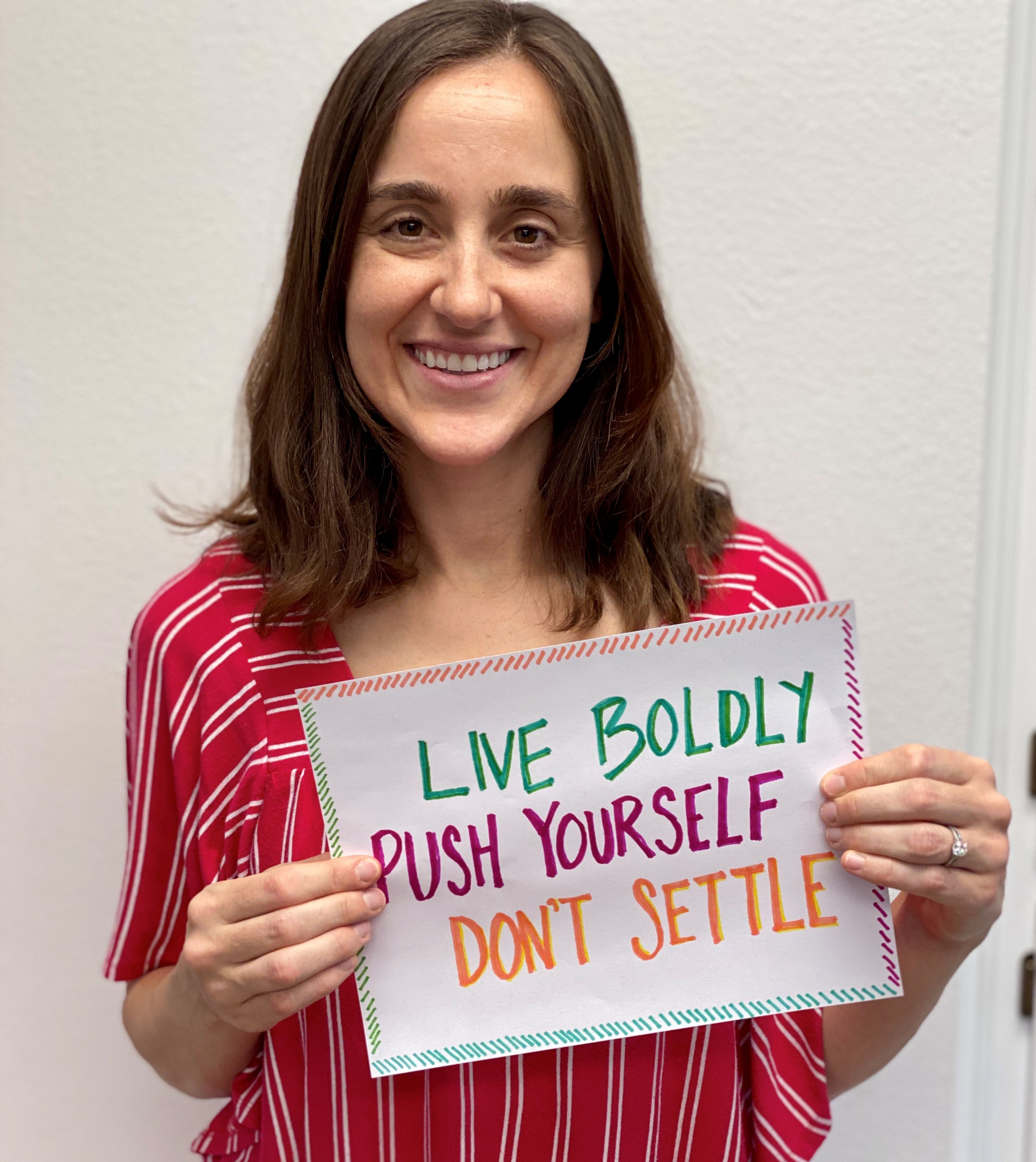 "Brittany is smiling, holding a handmade sign which says ""Live boldly, push yourself, don't settle."""