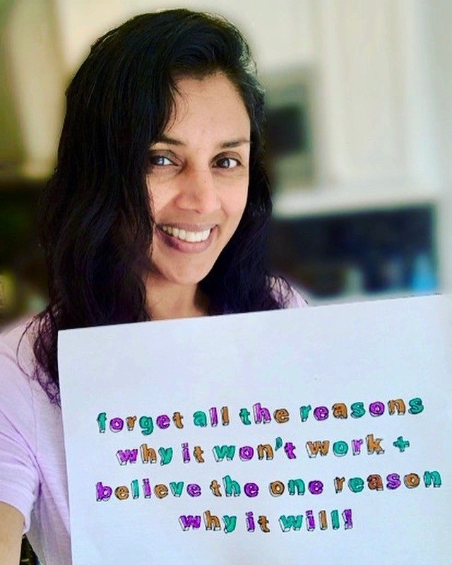 "Kamini is smiling, holding a handmade sign which says ""Forget the reasons why it won't work and believe the one reason why it will."""