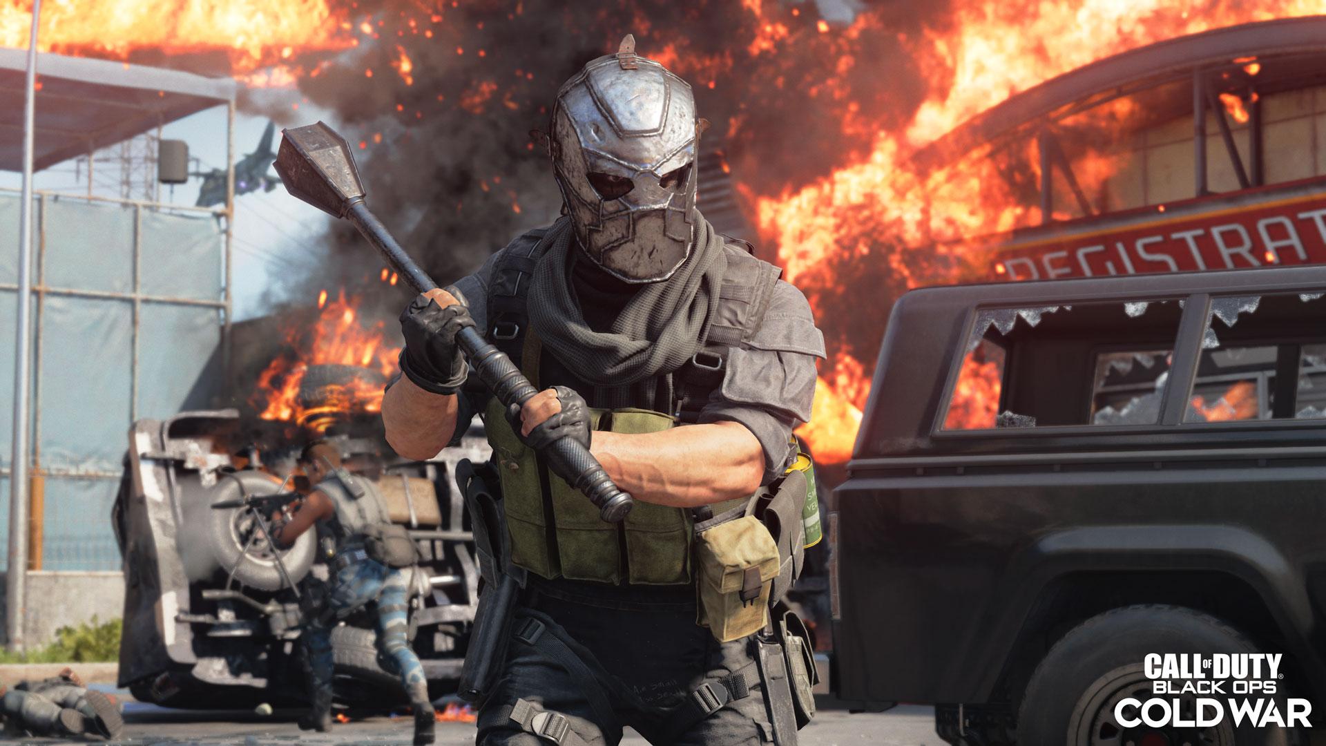 Brennende Autos hinter einem Mann mit einer Metallmaske